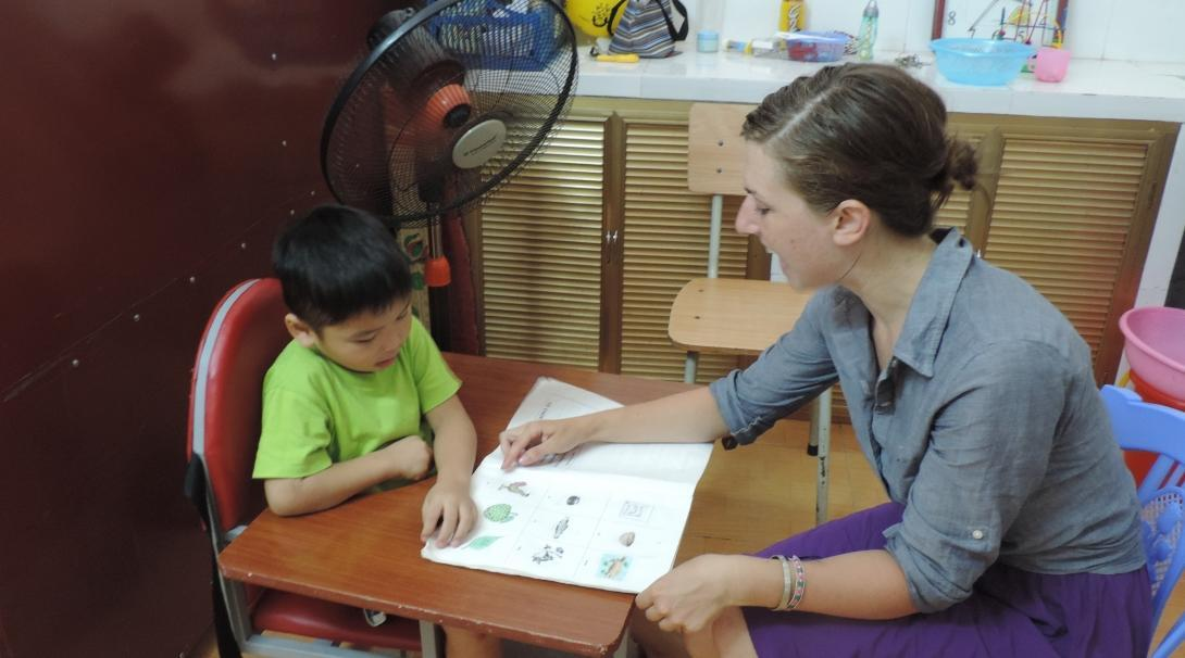 A local child looks at pictures with an Occupational Therapy intern in Vietnam.
